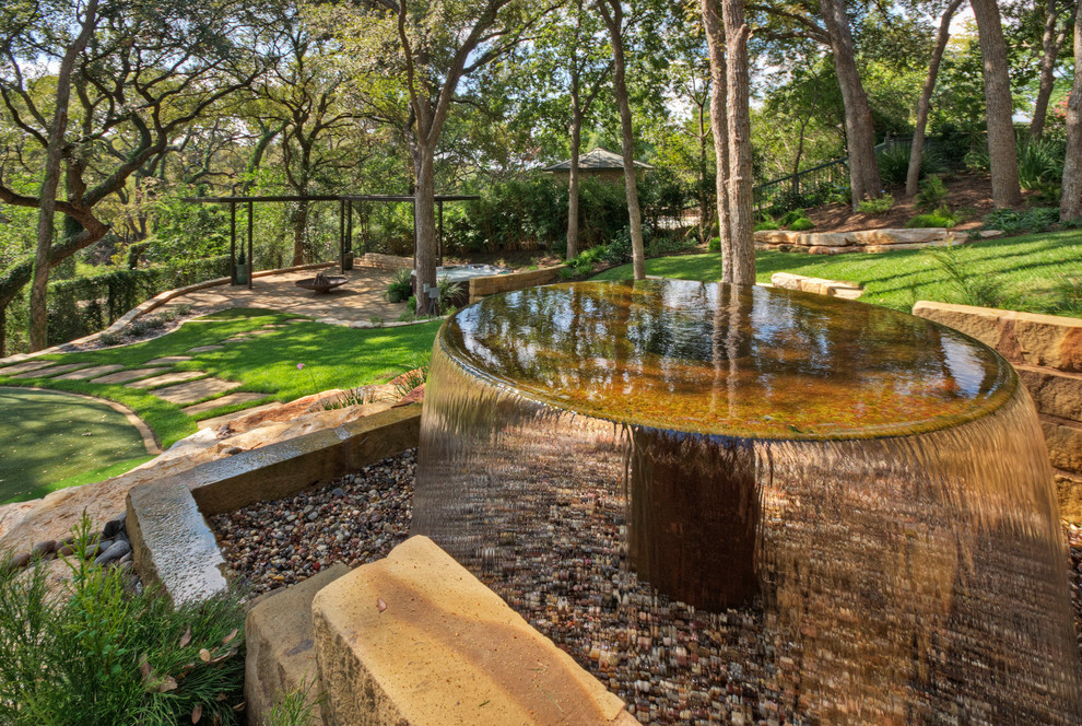 This is an example of a large traditional shade front yard stone landscaping in Austin for spring.