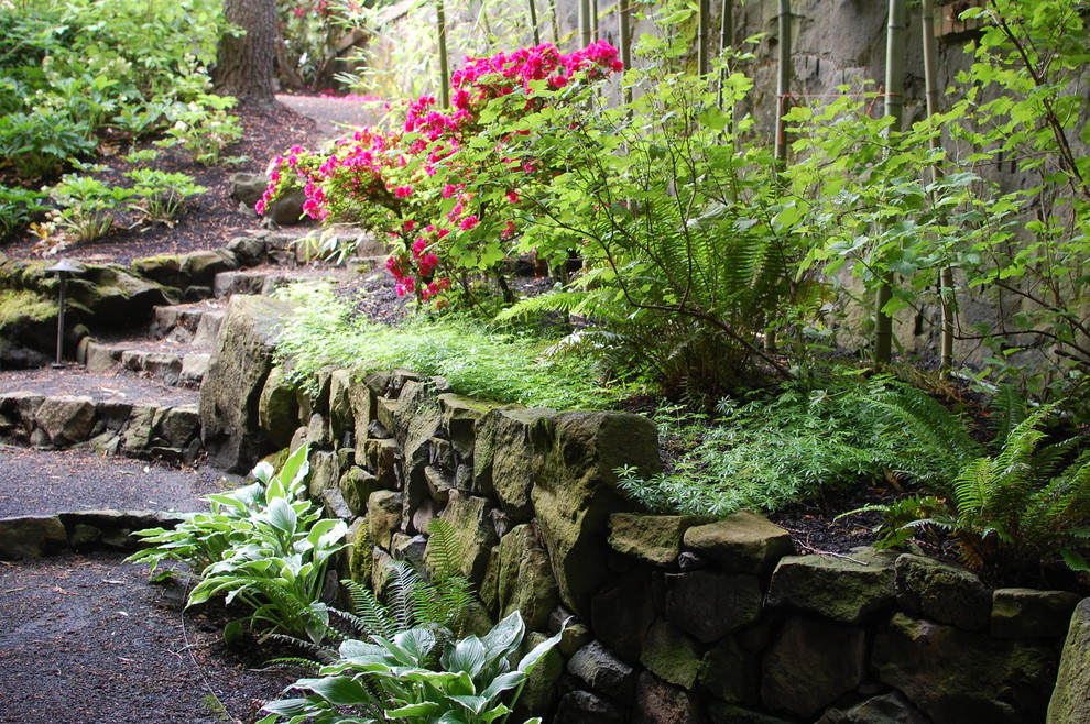 This is an example of a large eclectic partial sun backyard gravel retaining wall landscape in Portland.