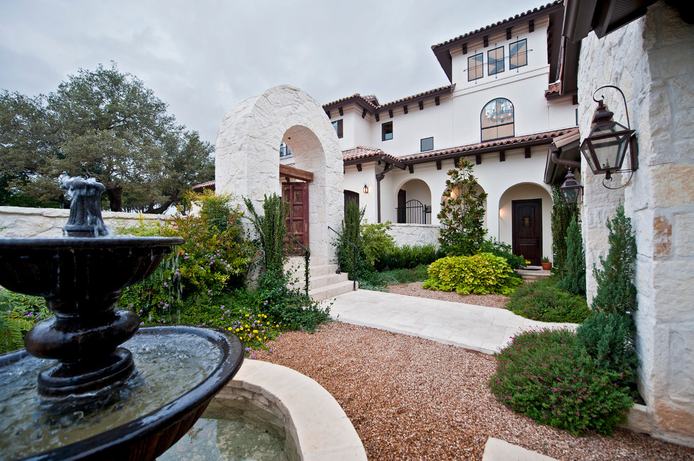 This is an example of a large mediterranean full sun backyard stone landscaping in Austin.