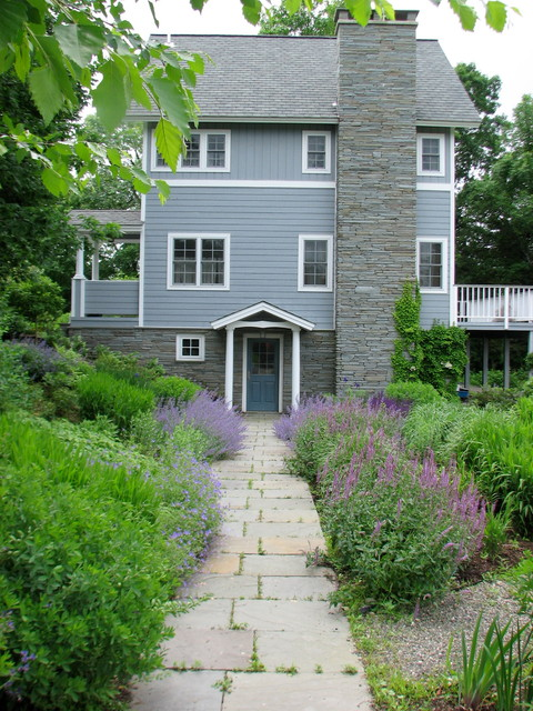 This is an example of a medium sized beach style front full sun garden in New York with natural stone paving and a garden path.