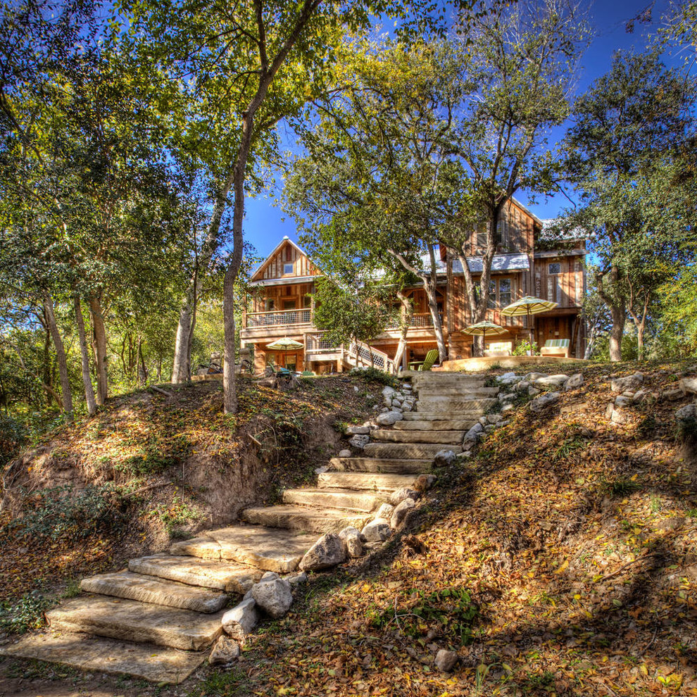 This is an example of a rustic shade hillside stone landscaping in Austin.
