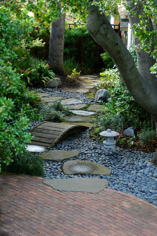 This is an example of a traditional shade backyard river rock water fountain landscape in San Francisco.