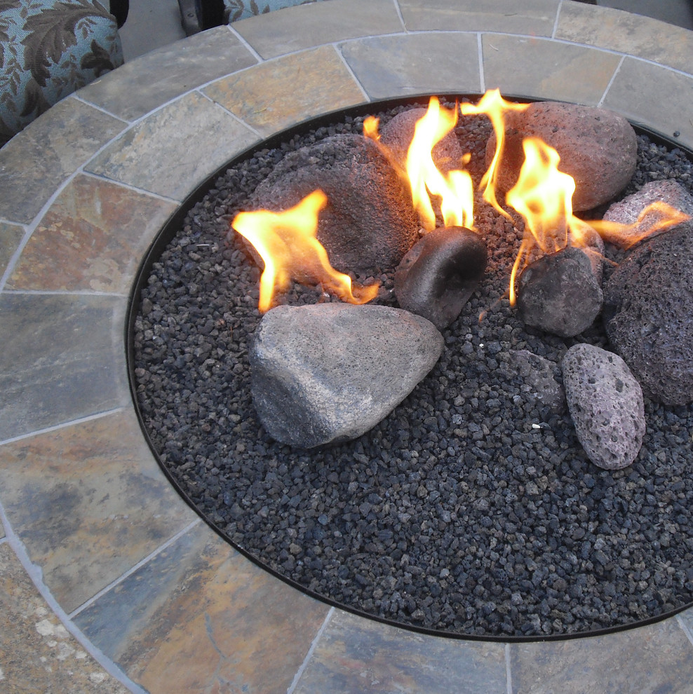 Design ideas for a huge mediterranean partial sun backyard stone landscaping in Seattle with a fire pit.