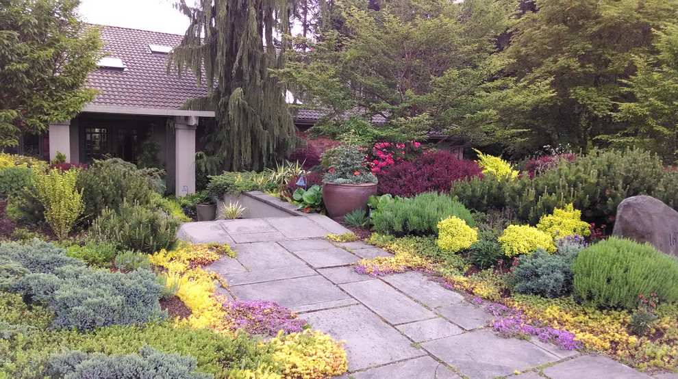 Photo of a large mediterranean full sun front yard stone retaining wall landscape in Seattle.