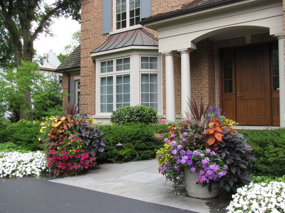 Inspiration for a large traditional full sun front yard stone landscaping in Chicago for summer.