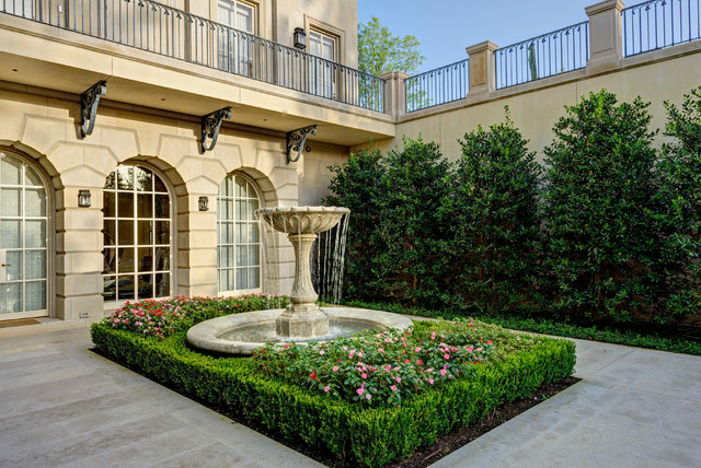 Photo of a traditional full sun side yard water fountain landscape in Dallas.