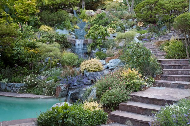 Swimming pool and hillside rock garden with waterfall for Pool design hillside
