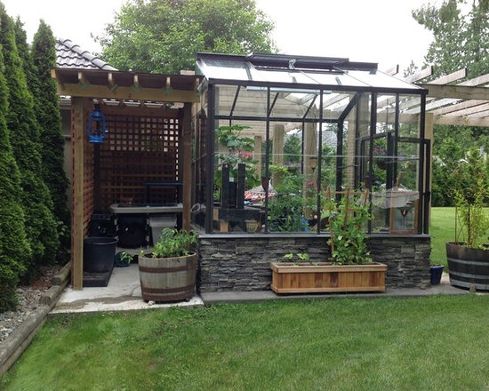 The Legacy 8x8 Greenhouse with Potting Shed - What a cute combination!  Our customer sent in this photo of our 8x8 Legacy greenhouse with a beautiful rock knee wall plus potting shed.  She wrote in to say that she loves the greenhouse so much she wanted to keep the dirt outside :)