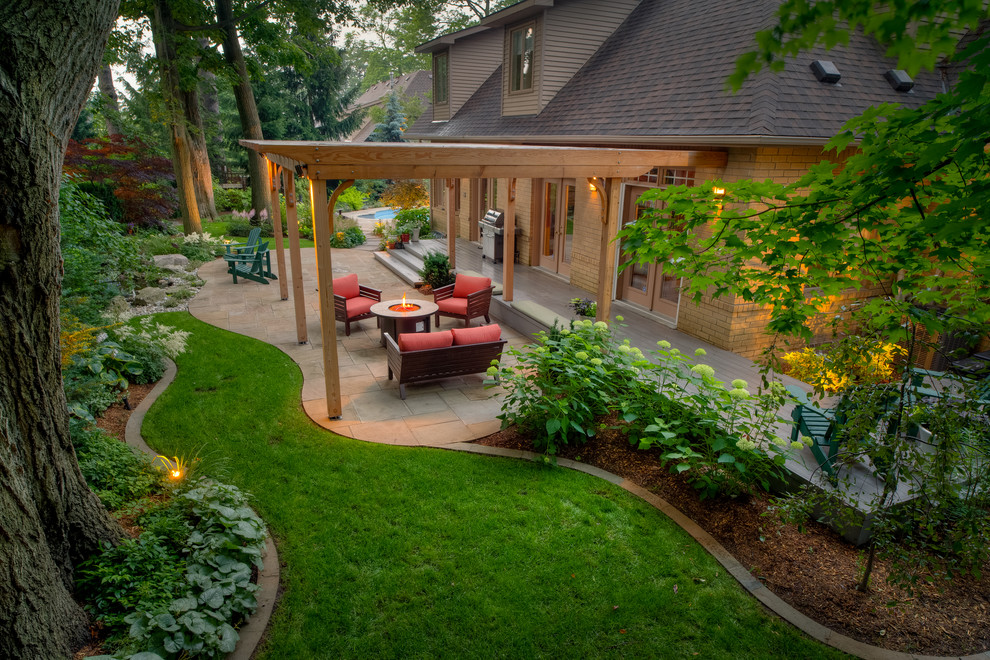 Photo of a large traditional backyard stone landscaping in Toronto.