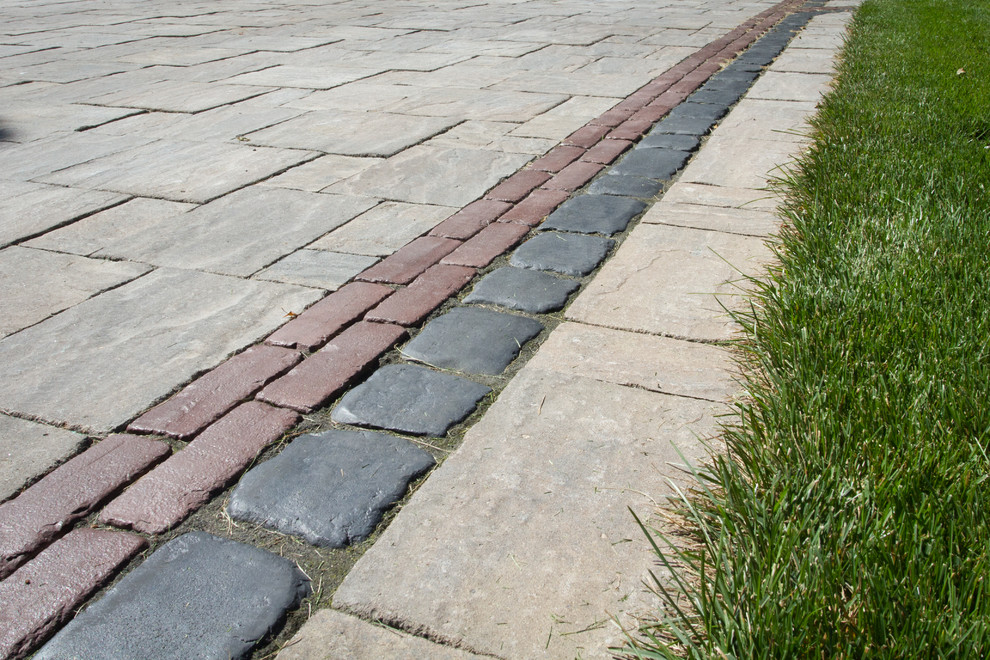Photo of a mid-sized contemporary partial sun front yard stone driveway in Toronto for spring.