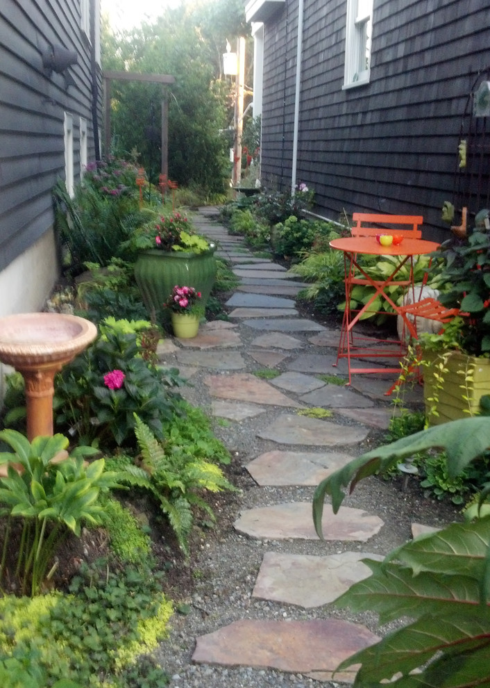 Photo of a small eclectic shade side yard stone landscaping in Seattle.
