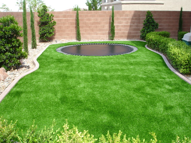 Trampoline surrounded by sythetic turf. traditional