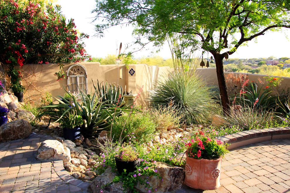 This is an example of a mid-sized mediterranean drought-tolerant, partial sun and desert backyard brick landscaping in Phoenix for summer.