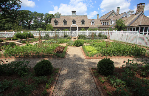 Here is a massive vegetable garden, over a large yard. The sections are spread wide apart, and the ample space is used to make maintaining the garden easy and manageable.