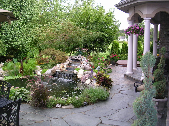 Veranda with pond mediterranean landscape chicago for Stone koi pond