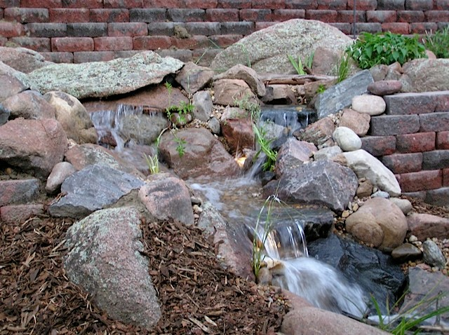 Water features through walls traditional landscape for Koi pool water gardens thornton
