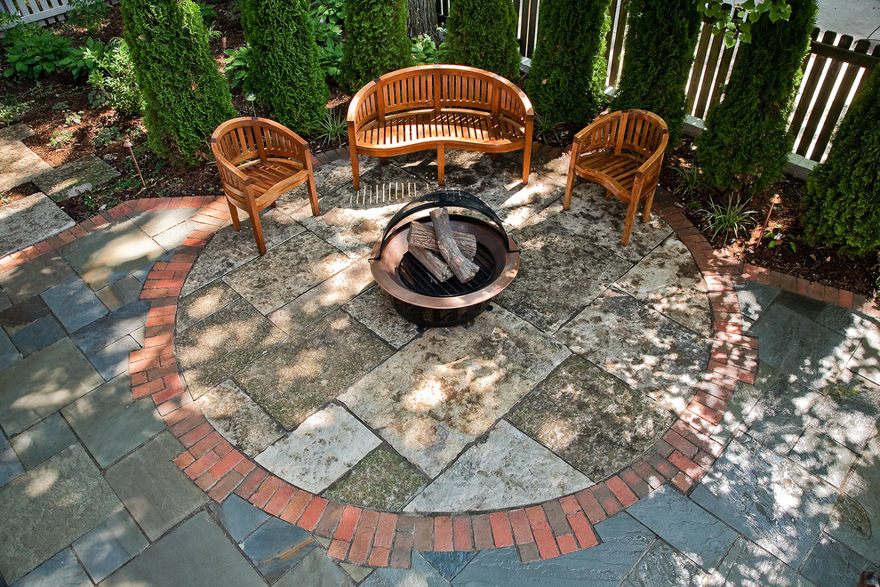 This is an example of a mid-sized traditional shade backyard stone landscaping in Milwaukee with a fire pit.