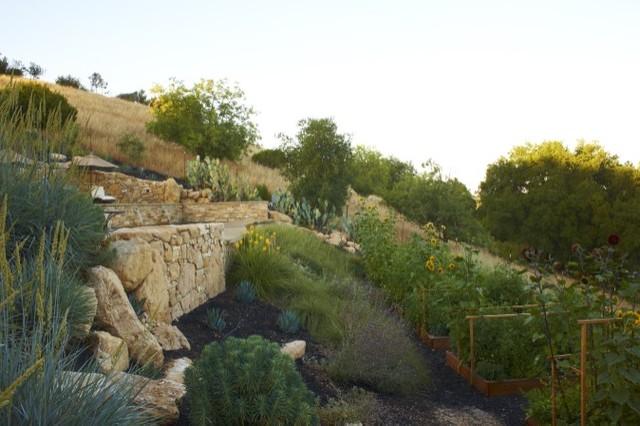 Ejemplo de jardín de secano, mediterráneo, grande, en ladera, con exposición parcial al sol y adoquines de piedra natural