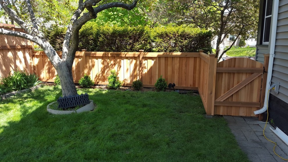 Photo of a large traditional partial sun backyard stone landscaping in Minneapolis.