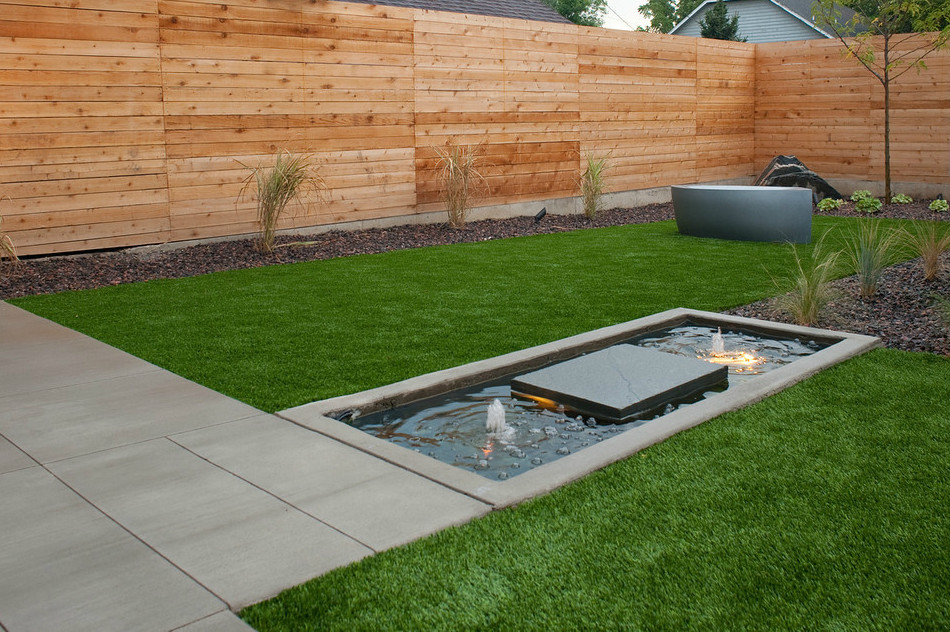 Design ideas for a mid-sized modern full sun backyard concrete paver landscaping in Denver with a fire pit.