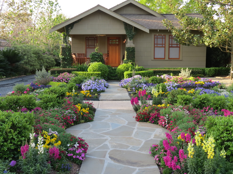 Photo of a mid-sized craftsman front yard stone flower bed in Houston for summer.