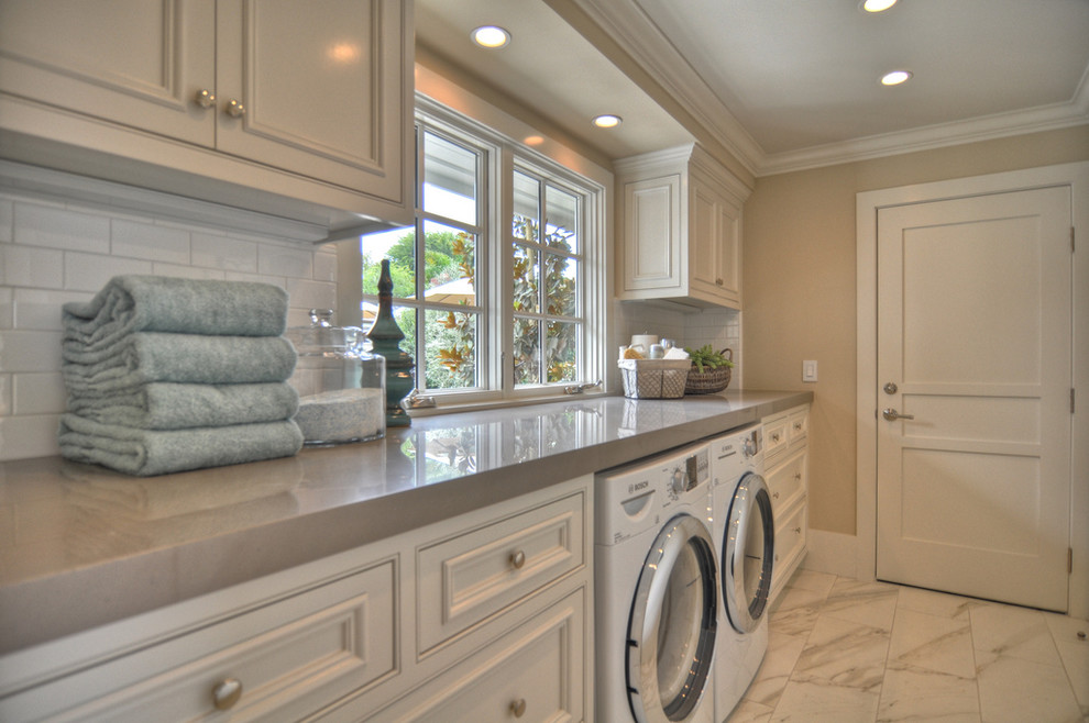 Beach style white floor laundry room photo in Los Angeles with white cabinets and gray countertops