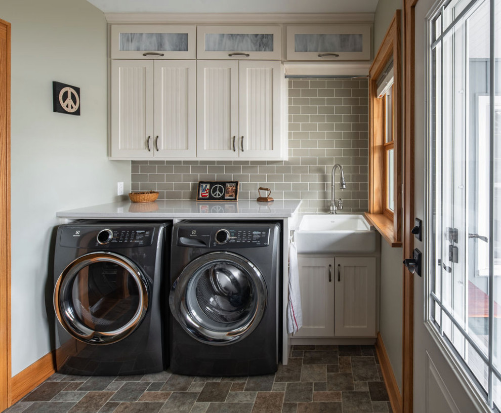 Inspiration for a mid-sized timeless single-wall vinyl floor and multicolored floor dedicated laundry room remodel in Columbus with a farmhouse sink, recessed-panel cabinets, white cabinets, quartz countertops, green walls, a side-by-side washer/dryer and white countertops