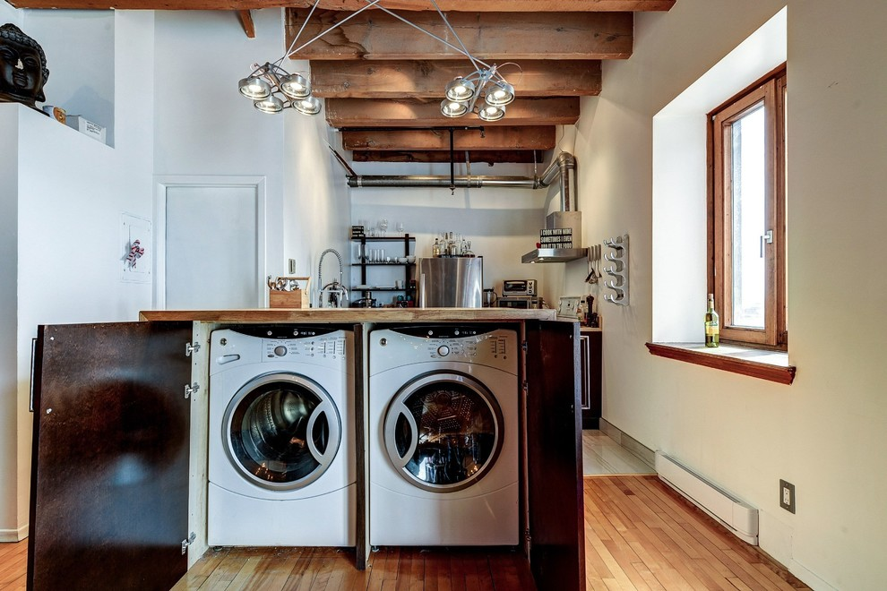 Example of a small urban medium tone wood floor laundry closet design in Montreal with a side-by-side washer/dryer, flat-panel cabinets, medium tone wood cabinets, wood countertops and white walls