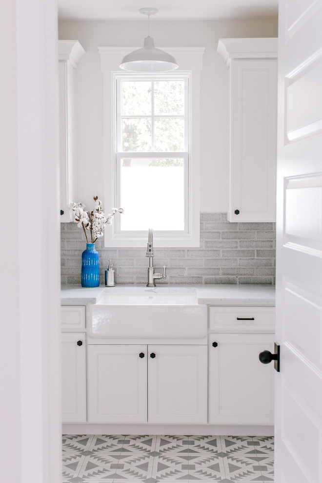 Farmhouse l-shaped concrete floor dedicated laundry room photo in Phoenix with a farmhouse sink, white cabinets, marble countertops, gray walls and a side-by-side washer/dryer