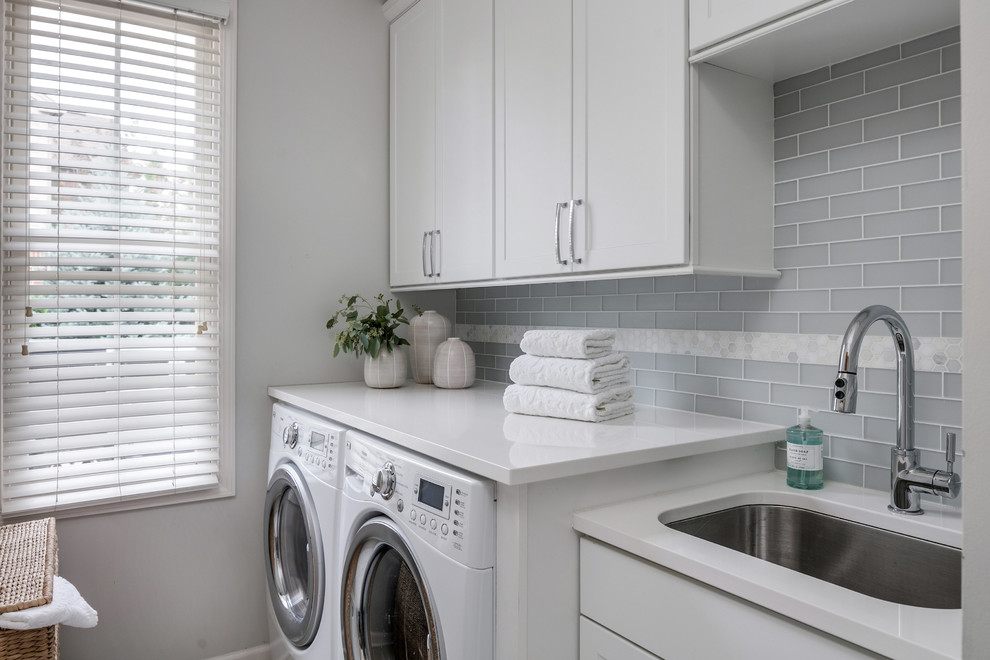 Inspiration for a mid-sized transitional single-wall dedicated laundry room remodel in Detroit with an undermount sink, shaker cabinets, white cabinets, quartz countertops, gray walls, a side-by-side washer/dryer and gray countertops
