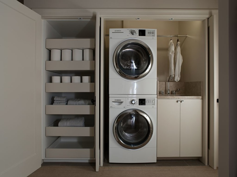 Inspiration for a small contemporary single-wall laundry closet remodel in San Francisco with a stacked washer/dryer, an undermount sink, flat-panel cabinets, beige cabinets and beige walls