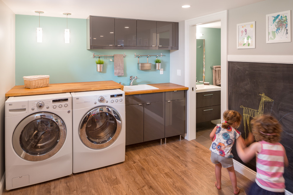 Example of a trendy laundry room design in Portland with gray cabinets, blue walls, wood countertops and brown countertops