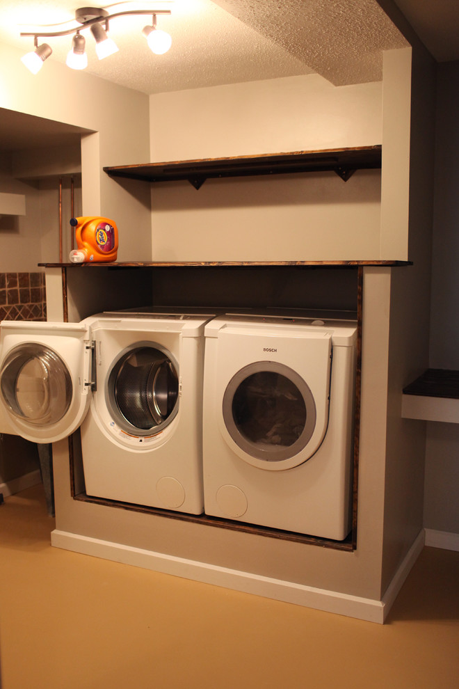 Example of a mid-sized classic u-shaped concrete floor utility room design in Minneapolis with an utility sink, flat-panel cabinets, dark wood cabinets, wood countertops, gray walls and a side-by-side washer/dryer