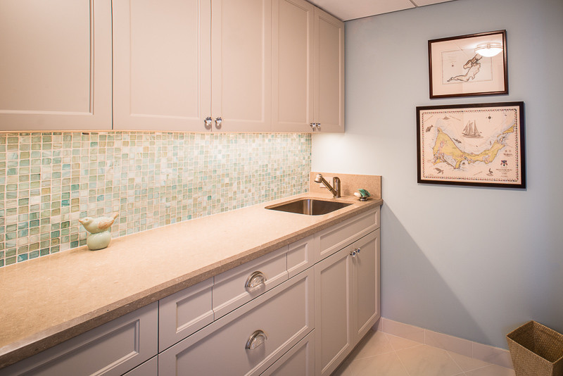 Inspiration for a mid-sized transitional single-wall ceramic tile and beige floor utility room remodel in Houston with an undermount sink, beaded inset cabinets, white cabinets, limestone countertops and blue walls
