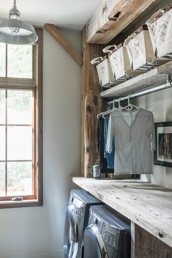 Example of a mid-sized mountain style dark wood floor and gray floor dedicated laundry room design in Other with open cabinets, medium tone wood cabinets, wood countertops, white walls and a side-by-side washer/dryer
