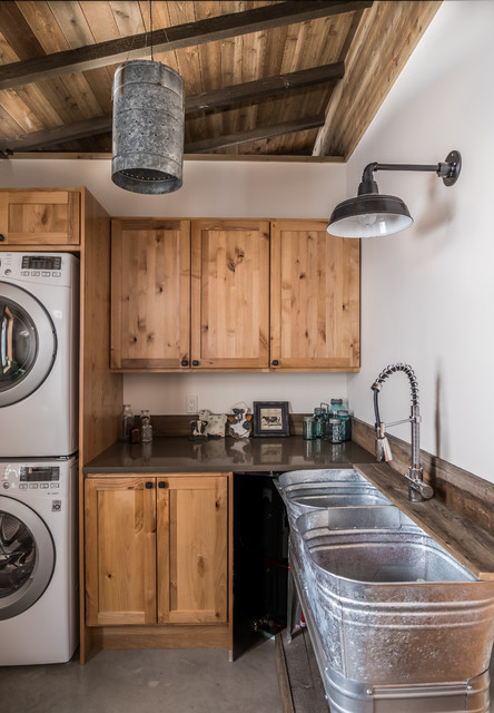 Inspiration for a mid-sized rustic l-shaped gray floor and concrete floor dedicated laundry room remodel in Seattle with an utility sink, shaker cabinets, white walls, a stacked washer/dryer, gray countertops, medium tone wood cabinets and solid surface countertops