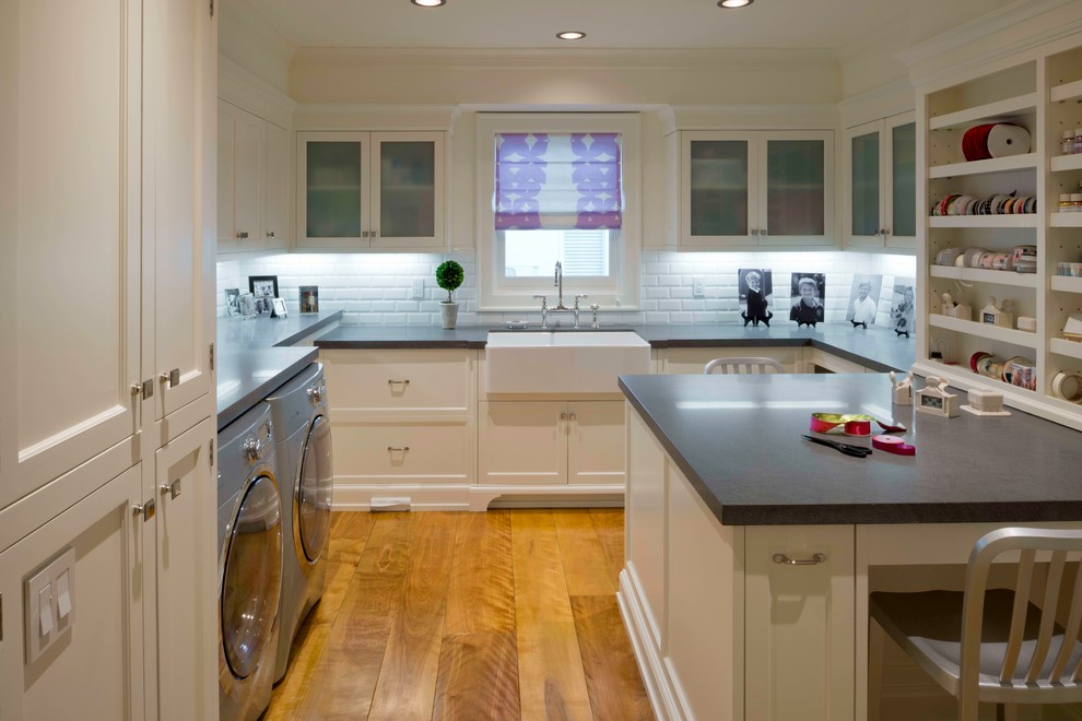 Example of a classic medium tone wood floor and orange floor laundry room design in Los Angeles with a farmhouse sink, white cabinets and white walls