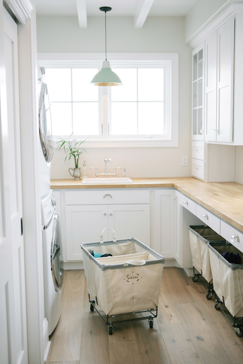 Large laundry room with rolling baskets featured on Remodelaholic.com