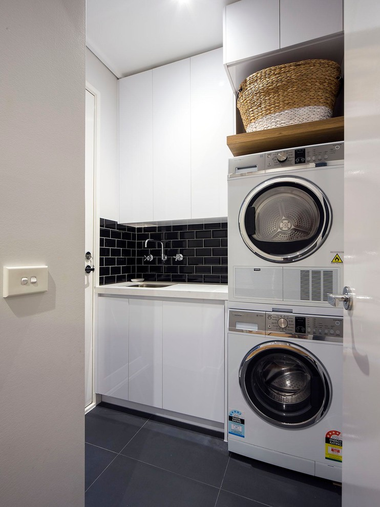 Inspiration for a small contemporary single-wall ceramic tile and gray floor dedicated laundry room remodel in Melbourne with white cabinets, granite countertops, a stacked washer/dryer, an undermount sink, flat-panel cabinets and gray walls