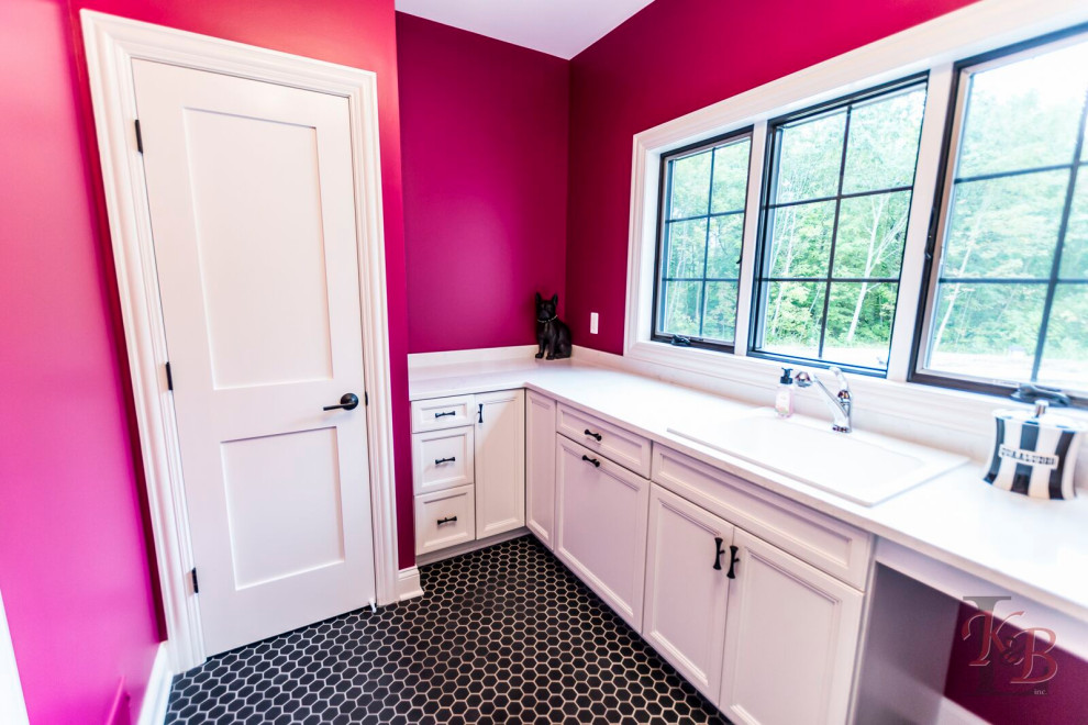 Inspiration for a galley ceramic tile and black floor dedicated laundry room remodel in Other with an utility sink, recessed-panel cabinets, pink walls, a side-by-side washer/dryer and white countertops