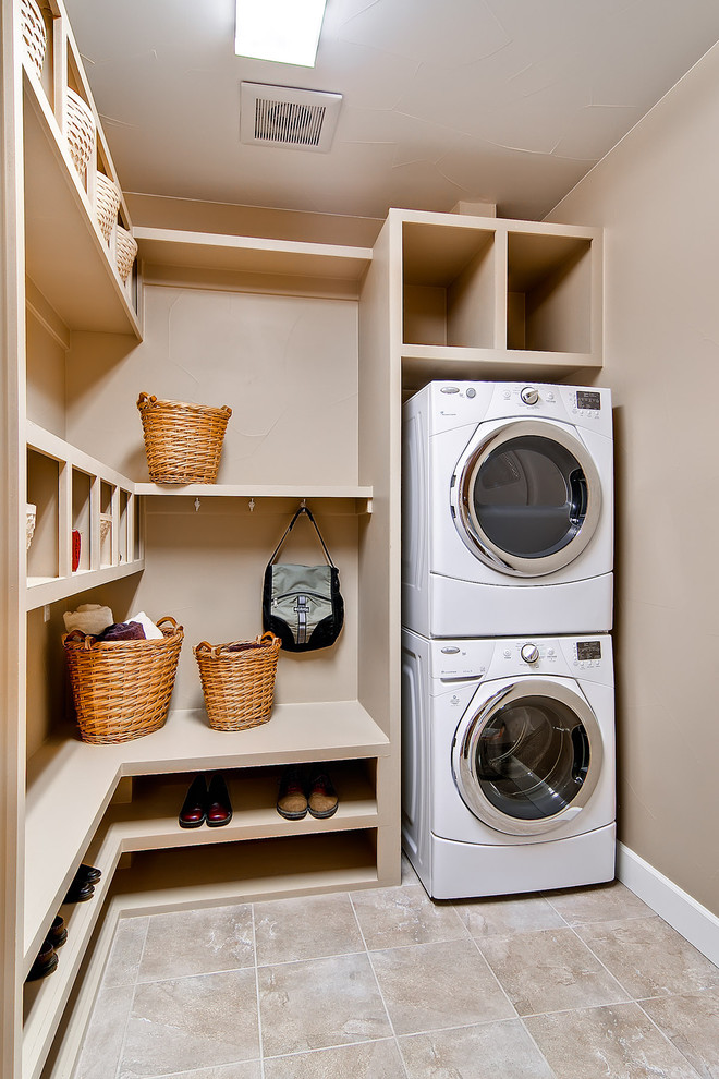Inspiration for a mid-sized timeless beige floor utility room remodel in Denver with a stacked washer/dryer and beige walls