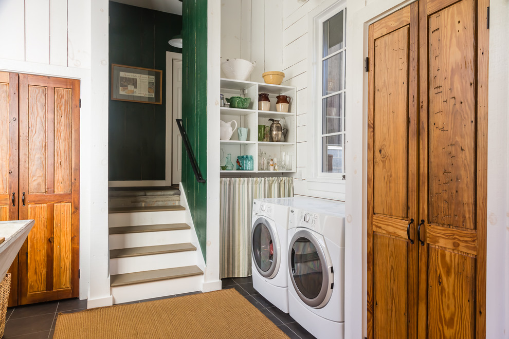 Example of a mid-sized classic u-shaped ceramic tile utility room design in Raleigh with a side-by-side washer/dryer, medium tone wood cabinets and white walls