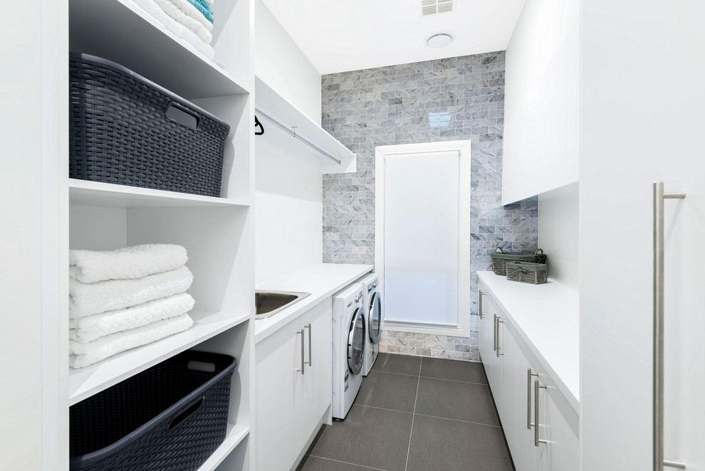 Example of a small trendy galley ceramic tile dedicated laundry room design in Melbourne with a drop-in sink, white walls, flat-panel cabinets, white cabinets and a side-by-side washer/dryer