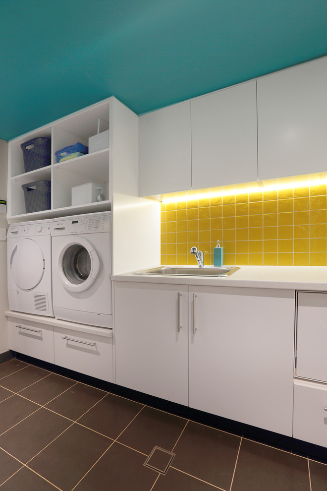 Mid-sized trendy single-wall ceramic tile dedicated laundry room photo in Sydney with a drop-in sink, flat-panel cabinets, white cabinets, laminate countertops and a side-by-side washer/dryer