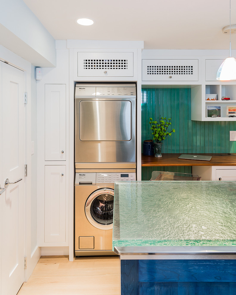 Dedicated laundry room - mid-sized transitional light wood floor dedicated laundry room idea in Boston with white cabinets, glass countertops, green walls, a stacked washer/dryer, shaker cabinets and turquoise countertops