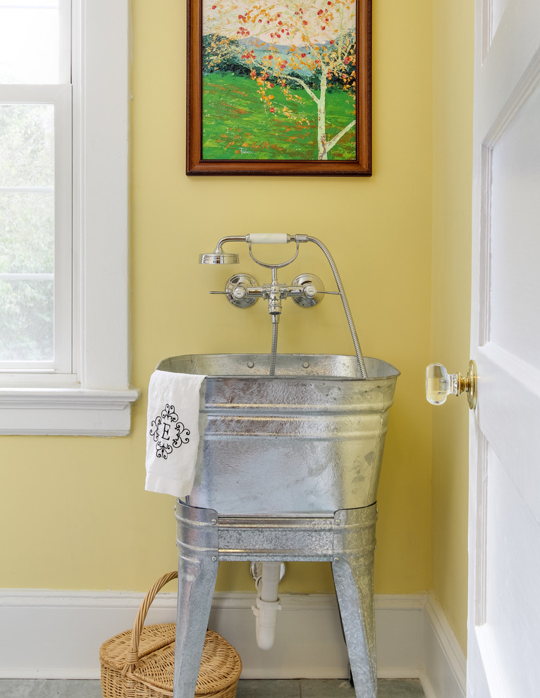 Example of a transitional laundry room design in Raleigh with an utility sink and yellow walls