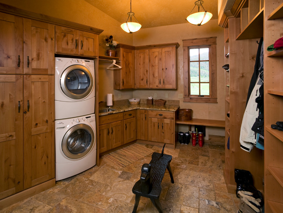 Laundry room - rustic laundry room idea in Denver with a stacked washer/dryer