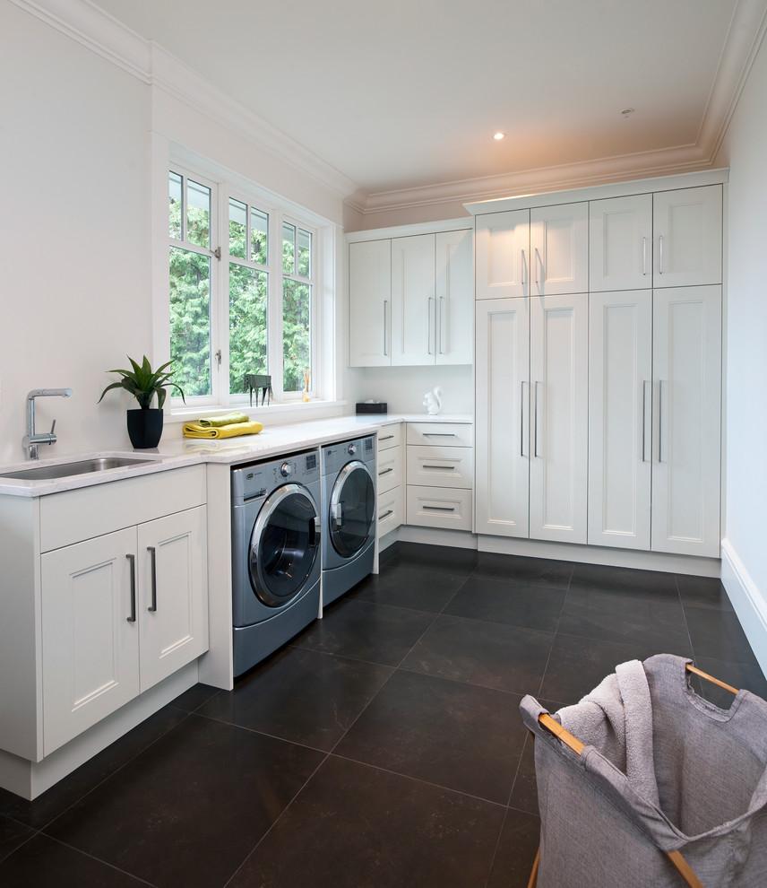 Trendy black floor laundry room photo in Vancouver
