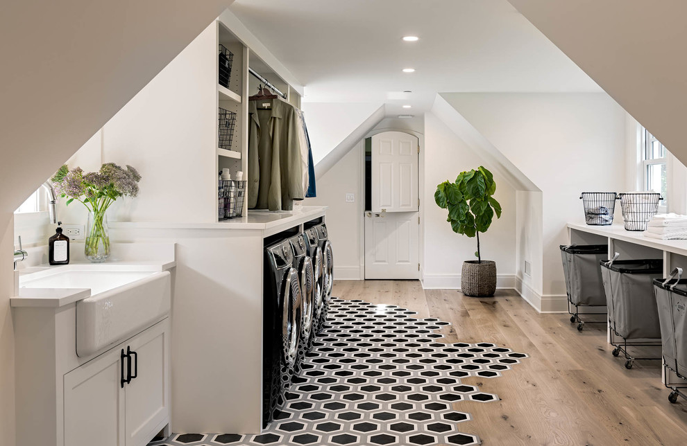 Inspiration for a mid-sized cottage galley medium tone wood floor and brown floor dedicated laundry room remodel in New York with a farmhouse sink, shaker cabinets, white cabinets, white walls and a side-by-side washer/dryer