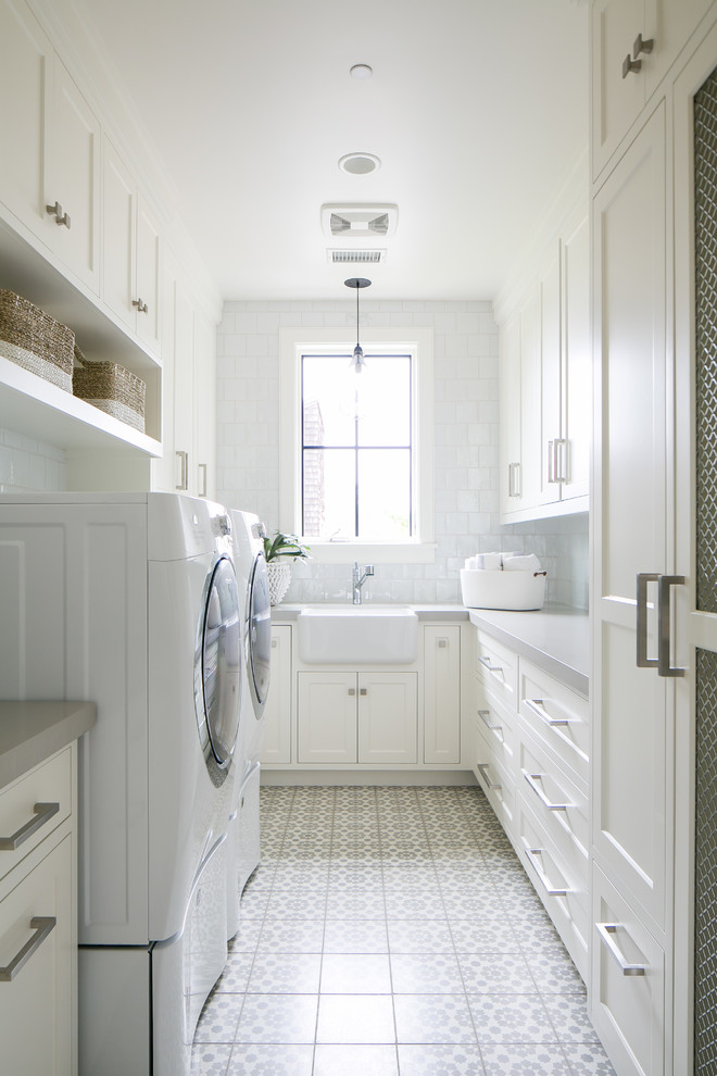 Coastal u-shaped white floor dedicated laundry room photo in Orange County with a farmhouse sink, recessed-panel cabinets, white cabinets, white walls and gray countertops